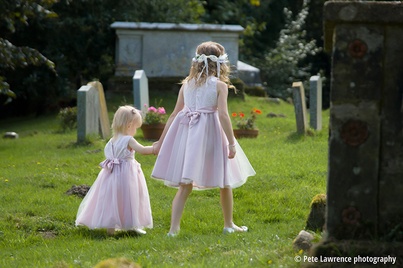 young-bridesmades-playing-in-churchyard